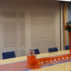 Seinällä isoja kuviollisia pöytäliinoja. Liinat on kudottu kangaspuissa.