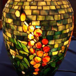 Pöydällä monivärinen valaisin. Valaisin on valmistettu pienistä lasinpaloista.