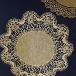 Pöydällä kaksi pyöreään pitsiliinaa. Liinojen keskellä on pyöreä pellavakangas ja pitsi on kiinnitetty kankaan reunaan. Piparkakkureunaisessa pitsissä kukkakuvioita.