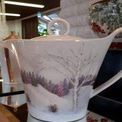 Pöydällä posliinikannu. Valoisen kannus sivuille on maalattu talvimaisema, jossa on koivu ja havumetsää.