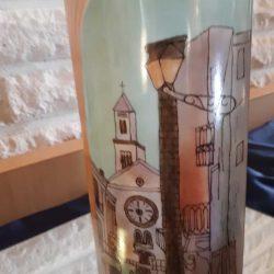 Pöydällä korkea kuviollinen vaasi. Vaasiin maalattu kirkko ja muita korkeita rakennuksia.