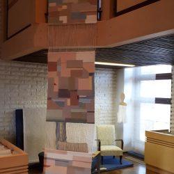 Valtuustosalin lehteriltä roikkuu kolmiosainen seinätekstiili. Tekstiilissä erivärisiä ja muotoisia ruutuja. Tekstiili on kudottu poppanakuteella kangaspuissa.