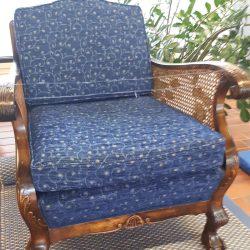 Lattialla iso puinen nojatuoli. Tuoli on verhoiltu pienikuvioisella sinisellä kankaalla.
