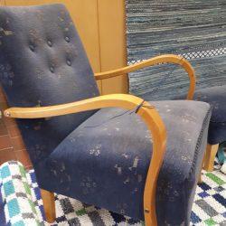 Lattialla käsinojallinen nojatuoli. Nojatuolin alla ruudullinen matto. Tuolin vieressä seinällä sinisävyinen räsymatto.