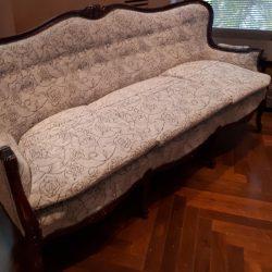 Lattialla koristeellinen sohva. Sohva on verhoiltu vaalealla kuviollisella kankaalla.