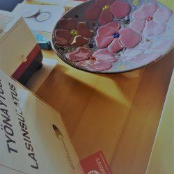 Pöydällä lasinen vati, jonka pinnassa on vaaleanpunaisia kukkia.