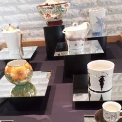Pöydällä lasilevyjen päällä posliiniesineitä. Iso liemikulho, kaksi isoa kannellista kannua, kolme vaasia ja kahvikuppi. Esineiden pintaan maalattu kukkia ja maisemia.