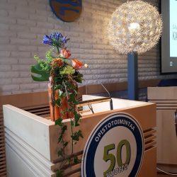 Valtuustosalissa puhujapönttö, jonka päällä kukka-asetelma. Edessä pyöreä merkki, jossa lukee Säkylän kansalaisopisto 50 vuotta.